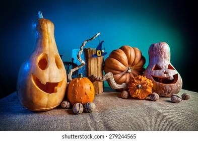Geschnitzte Kürbisse, altes Buch, Nüsse und Hexenhut aus Filz auf dem Ast bei Halloween-Party