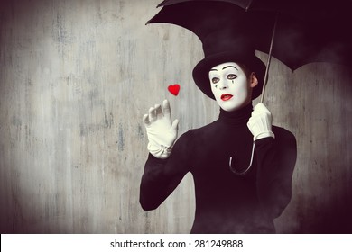 Portrait of a male mime artist standing under umbrella expressing sadness and loneliness. Love. Grunge background.