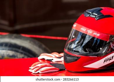 レーシングカーに乗るための手袋と赤いヘルメット