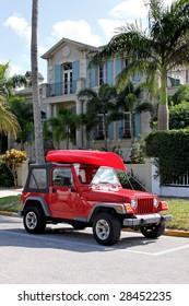 Jeep rojo con estacionamiento de kayak en frente de la casa
