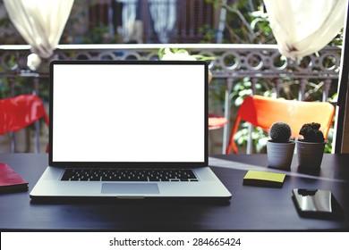 開いているコンピューター、カラフルなノートブックとステッカー、コンテンツやテキストメッセージ用の空白のコピースペースの空の画面を備えたラップトップ、夏の家のインテリアの開いているウィンドウのモダンなテーブル、フィルターのある職場