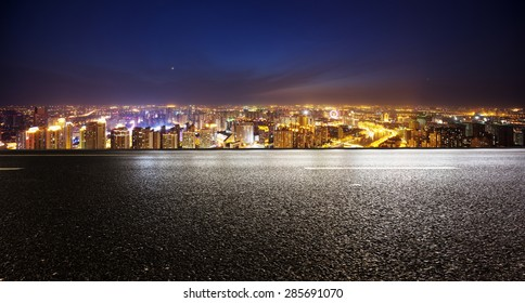 Leere Asphaltstraße und moderne Skyline bei Nacht