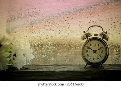 Retro Wecker auf Tabelle.10.10 Uhr und regnerischen Tag Fenster Hintergrund, Vintage-Stil