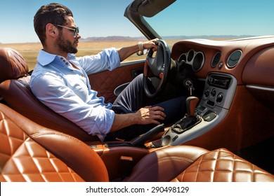 Hübscher Mann in der Nähe des Autos. Luxusleben.