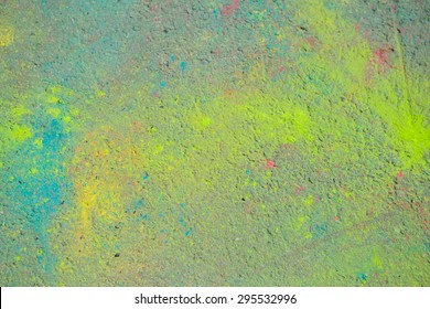 地面に散らばって横たわっている複数の色のカラフルなホーリーパウダーの背景。