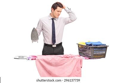 Foto de estudio de un joven confundido tratando de planchar su ropa aislado sobre fondo blanco.