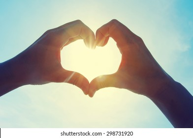 Weibliche Hände in Form eines Herzens gegen den Himmel passieren Sonnenstrahlen. Hände in Form des Liebesherzens