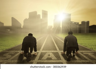 Geschäftswettbewerb: Rückansicht von zwei Arbeitern, die einen formellen Anzug tragen und auf der Startlinie knien, um an Wettkämpfen teilzunehmen
