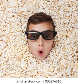 Surprise young boy in stereo glasses watching a movie from popcorn
