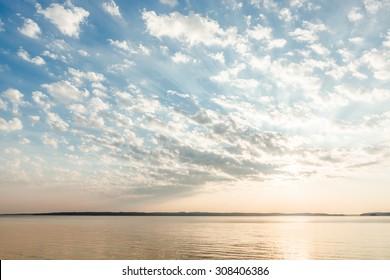 Wolken und Sonnenstrahlen über See bei Sonnenaufgang