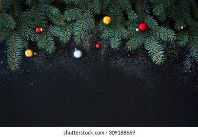 Weihnachts- oder Neujahrsdekorationshintergrund: Pelzbaumzweige, bunte Glaskugeln auf schwarzem Schmutzhintergrund mit Kopienraum