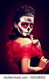 halloween maquillaje calavera de azúcar hermosa modelo con peinado perfecto. Concepto de santa muerte. Tonificación retro de moda.