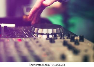 クラブDJがパーティーでビニールのターンテーブルで音楽をミキシング