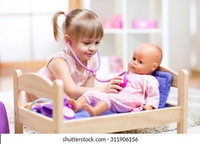 เด็กผู้หญิงกำลังเล่นหมอกับตุ๊กตาในโรงเรียนอนุบาล