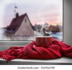 Tasse mit einem heißen Getränk auf der Fensterbank im Hintergrund einer Winterstadt. Konzentrieren Sie sich auf den Rand der Tasse
