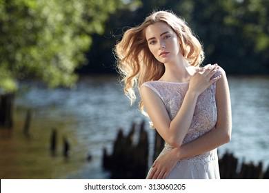 Novia modelo en la playa bajo el sol. Belleza, cabello, estilo.