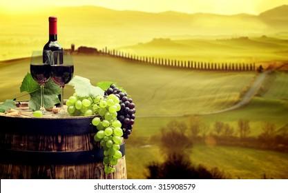 Botella de vino tinto y copa de vino en barril de madera. Hermoso fondo de la Toscana