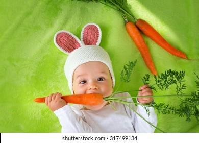 新鮮なニンジンを食べるウサギの帽子の赤ちゃん
