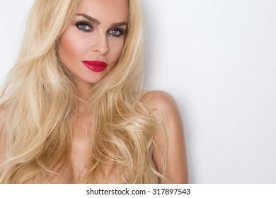 Schönheitsgesicht der jungen schönen Frau - lokalisiert auf weißem Hintergrund. Wunderschönes weibliches Porträt mit gekämmten blonden Haaren. Junges erwachsenes Mädchen mit gesunder Haut. Hübsche Dame mit Mode-Augen-Make-up.