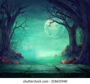 Fondo de Halloween. Bosque fantasmagórico con árboles muertos y calabazas y mesa de madera. Mesa de madera. Diseño de halloween con calabazas
