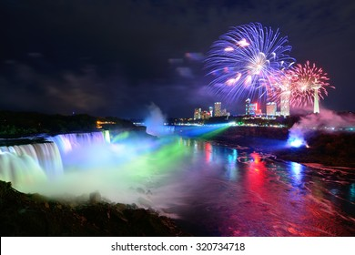 Niagara Falls lit at night by colorful lights with fireworks