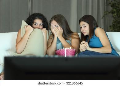 Las niñas viendo una película de terror en la televisión sentados en un sofá en casa