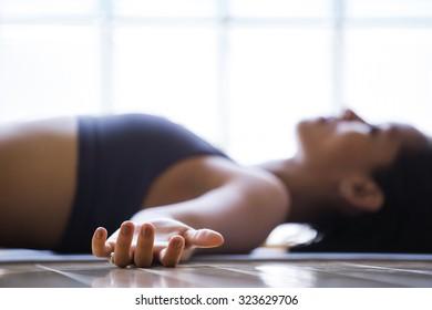 Young latin woman practicing meditation indoors.