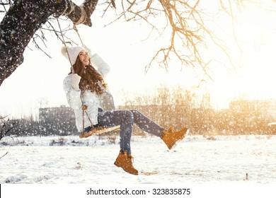 Glückliches Mädchen und Seilschaukel am sonnigen Wintertag