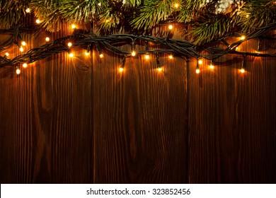 Weihnachtsbaumzweig und Lichter auf hölzernem Hintergrund. Ansicht mit Kopierplatz