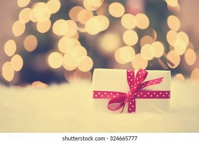 Weihnachtsgeschenkbox auf weißem Teppich vor Baum