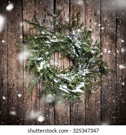 降る雪を描く木製の背景に緑の自然の花輪。ヴィンテージスタイル