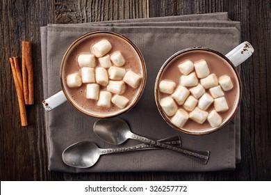 Dos tazas de chocolate caliente con malvaviscos y palitos de canela sobre fondo de madera