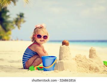 linda niña jugando con arena en la playa tropical
