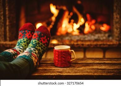 Füße in Wollsocken am Weihnachtskamin. Frau entspannt sich am warmen Feuer mit einer Tasse heißem Getränk und wärmt ihre Füße in Wollsocken auf. Nahaufnahme auf Füßen. Winter- und Weihnachtsferienkonzept.