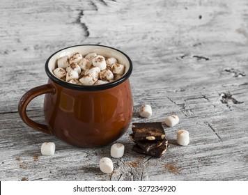 chocolate caliente con malvaviscos en una taza de cerámica sobre superficie de madera brillante