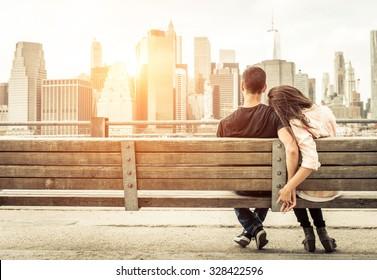 日没時にスカイラインの前にニューヨークのベンチでリラックスしたカップル。愛、関係、旅行についての概念