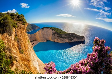 Navagio Strand mit Schiffbruch und Blumen gegen Sonnenuntergang in Griechenland