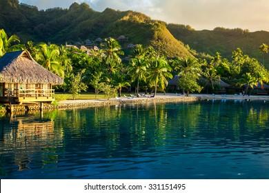 Villas en un resort tropical y con palmeras reflejadas en el océano durante la puesta de sol