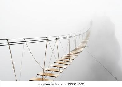 霧の中で消えるぶら下がっている橋の上を歩いているファジーな男。橋の真ん中に焦点を当てます。