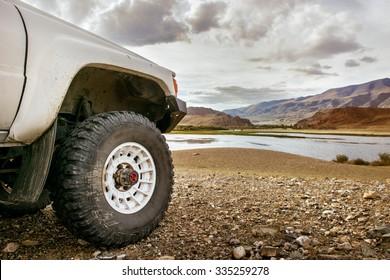 山の湖の背景に立っている大きなSUV車のホイール