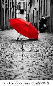 Rode paraplu op geplaveide straat in de oude stad. Wind, regen, stormachtig weer. Kleur in zwart-wit conceptueel, idee. Vintage, retro stijl.