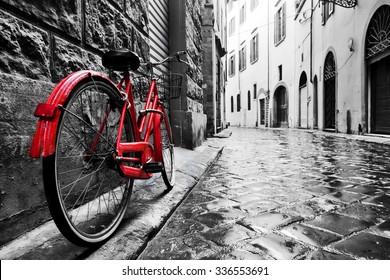 Retro vintage rode fiets op geplaveide straat in de oude stad. Kleur in zwart en wit. Oud charmant fietsconcept.