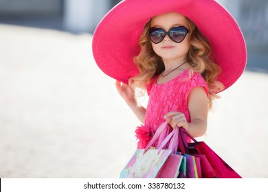 cute little girl in fashionable hat on shopping. portrait of a kid with shopping bags. child in dress, sunglasses and shoes near shopping mall having fun. shopping. girl. fashion