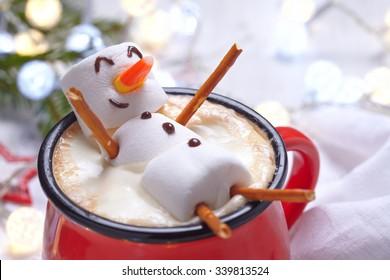 Roter Becher mit heißer Schokolade mit geschmolzenem Marshmallow-Schneemann