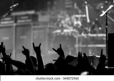 Eine Menge Fans, die sich während eines Konzerts freuen und die Teufelshörner hochwerfen