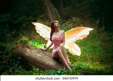 ピンクのドレスを着た小さな妖精、透明な金色のピンクの輝く翼、ファッションの創造的な色、幻想的な射撃森のニンフ蝶が丸太の上に座っています。自然の調和の妖精の女神。