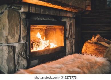 Warmer gemütlicher Kamin mit echtem Holzofen. Gemütliches Winterkonzept. Weihnachts- und Reisehintergrund mit Platz für Ihren Text.