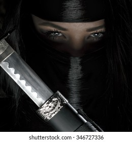 Girl or woman in black ninja samurai warrior outfit holds katana sword. Female assassin with a weapon.