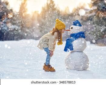 glückliches Kindermädchen plaing mit einem Schneemann auf einem verschneiten Winterspaziergang