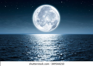Vollmond steigt nachts über leerem Ozean mit Kopierraum auf